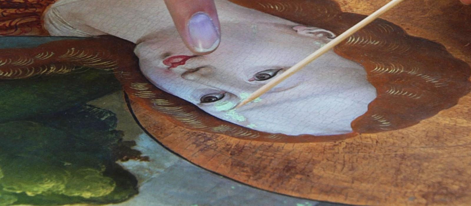 Restaurierungsarbeiten an einem Gemälde. zu sehen ist der vergrößerte Kopf einer Heiligendarstellung