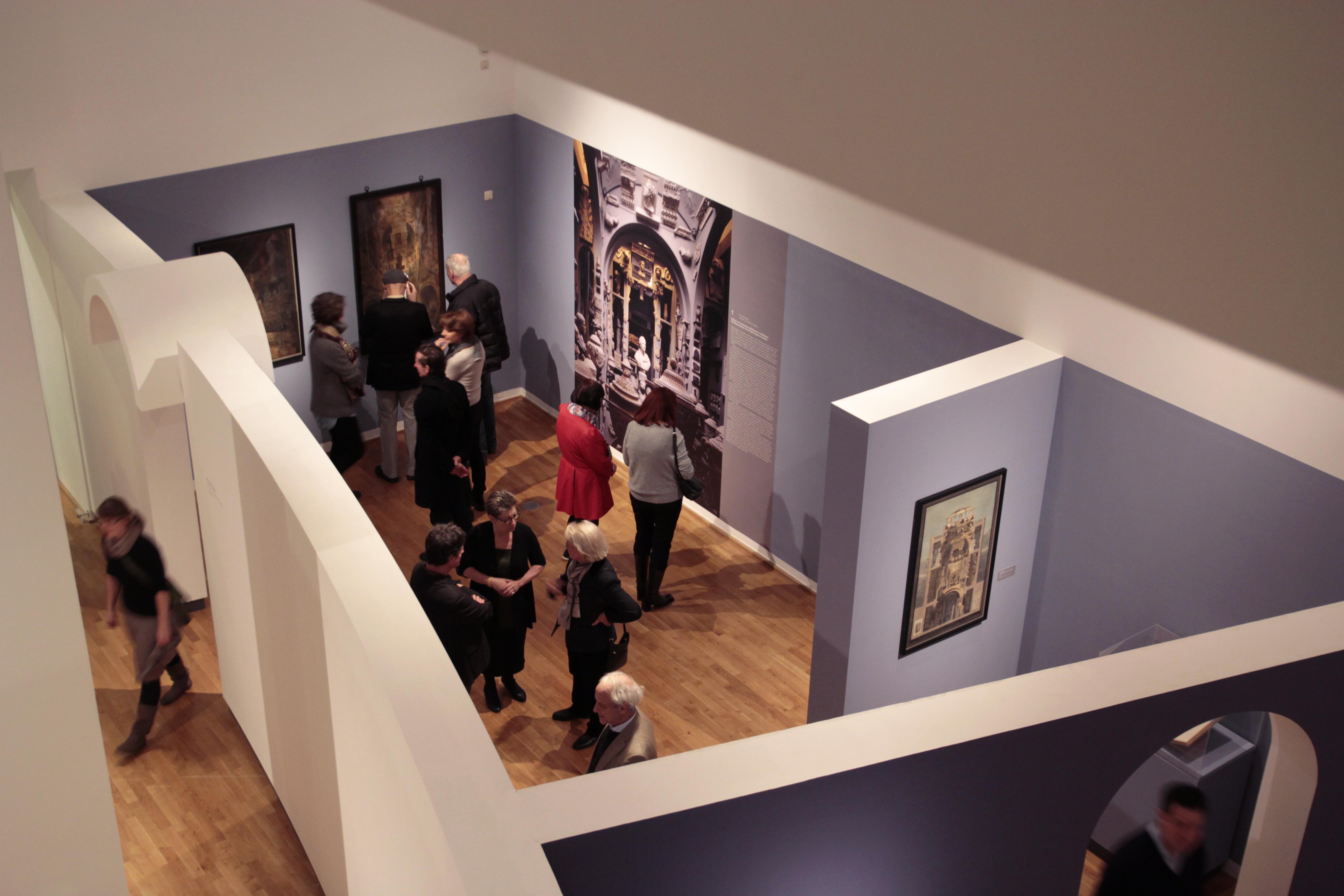 Ansicht von oben: Menschen betrachten eine Ausstellung