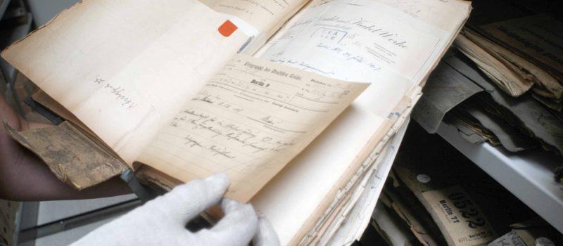 Akten werden mit behandschuhter Hand umgeblättert