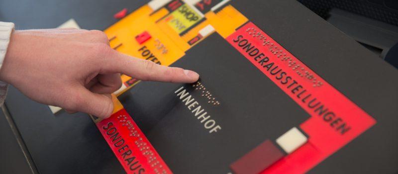Finger eines Besuchers auf Beschriftungstafel in Brailleschrift