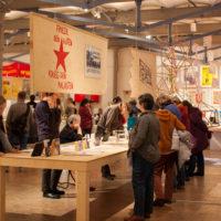 Menschen schauen sich Transparente in einer Ausstellung an