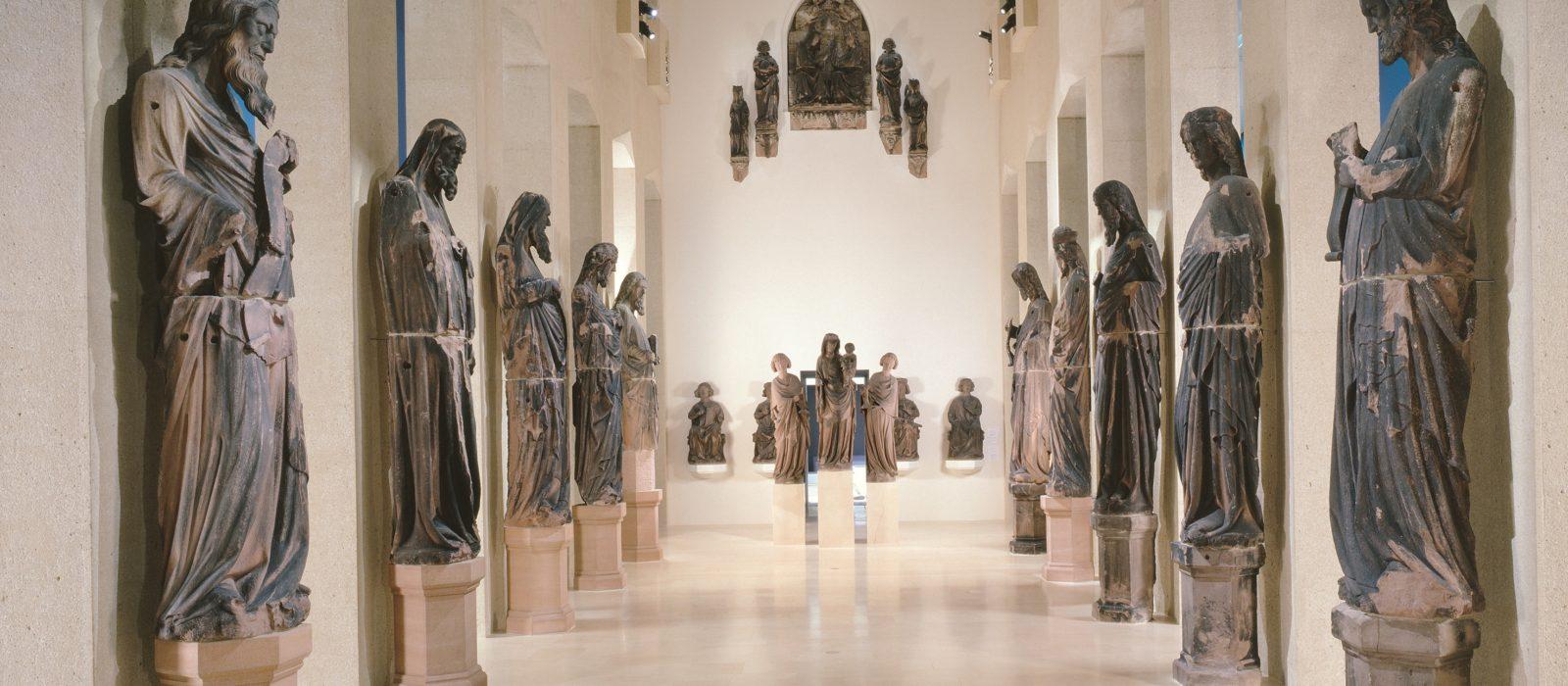 Ein langer Gang mit Skulpturen links und rechts gesäumt
