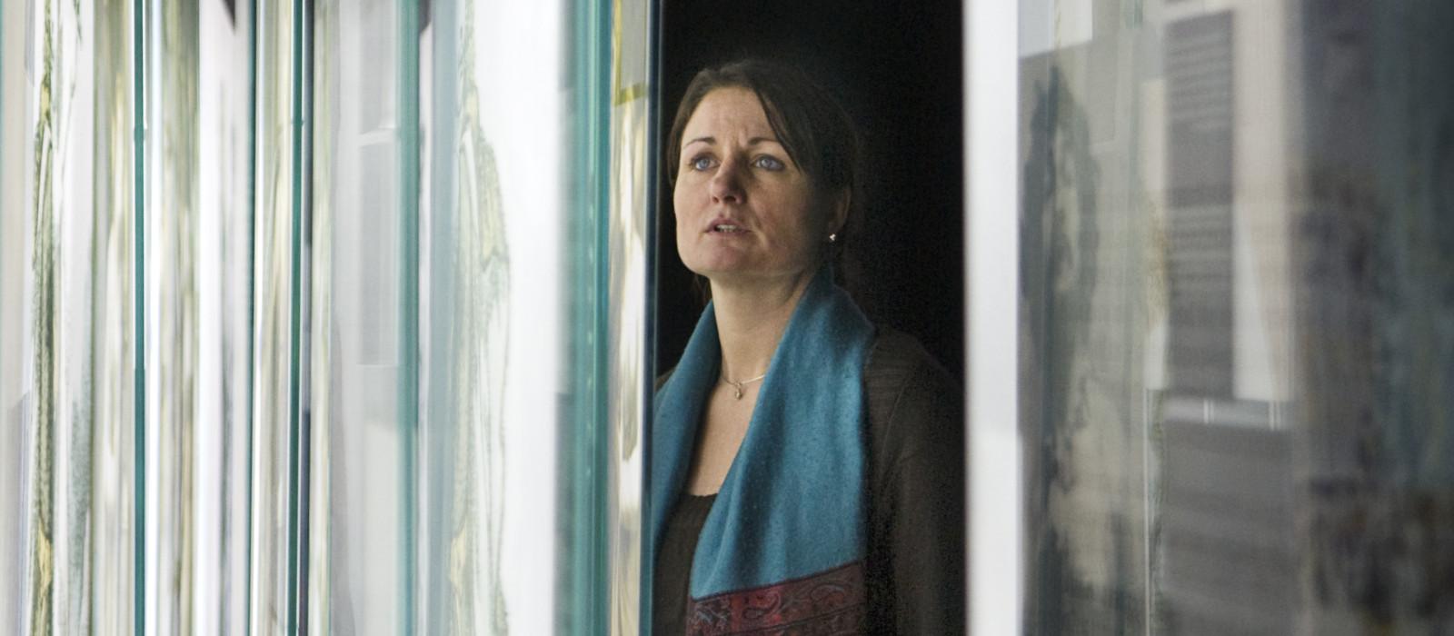 Eine Frau blickt in einen Ausstellungsraum