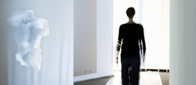 Eine Frau geht durch einen Ausstellungsraum