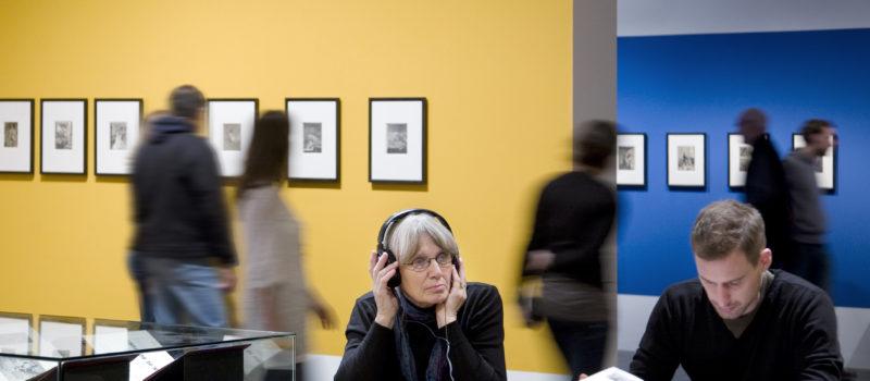 Ein Ausstellungsraum. Im Vordergrund zwei Personen mit Ausstellungskatalog und AudioGuide