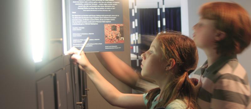 Zwei Kinder im Museum bei der Betrachtung einer Texttafel