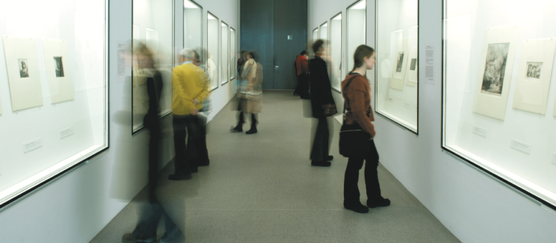 Personen bei der Betrachtung von Ausstellungsvitrinen