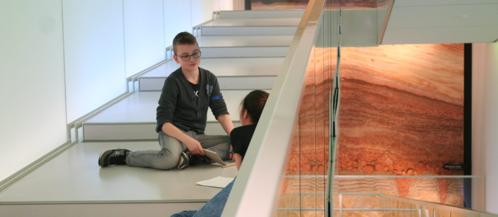 Zwei Kinder auf den Stufen des Museums mit Stift und Notizblock