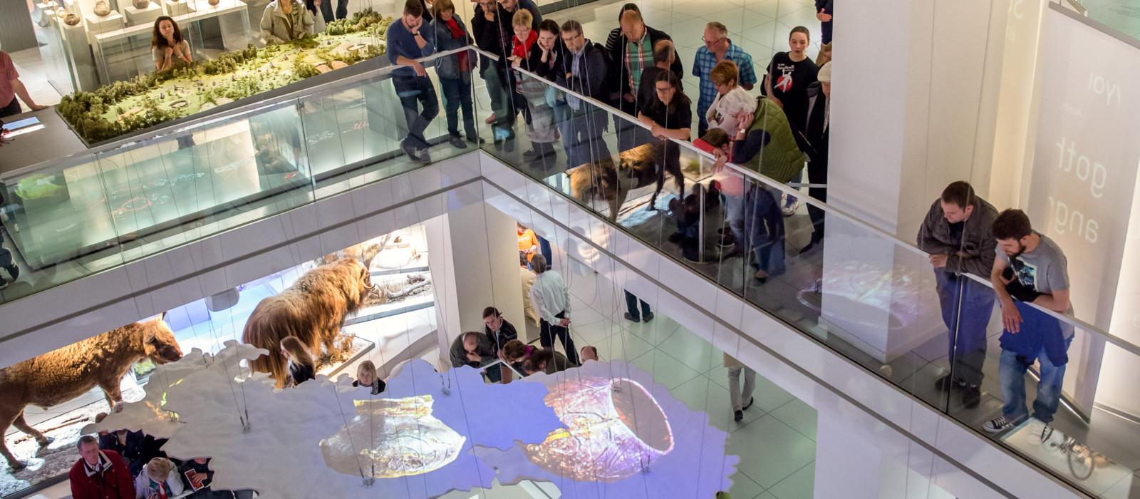 Einblick in eine mehrgeschossige Ausstellung mit schwebender Karte