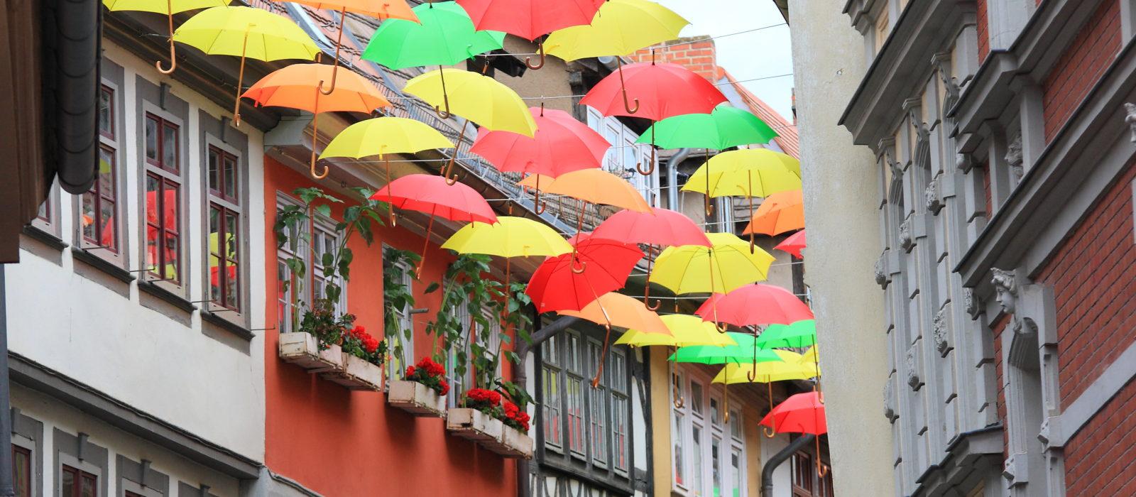 Die Krämerbrücke in Erfurt, bunte, aufgepannte Regenschirme zwischen Häuserfassaden