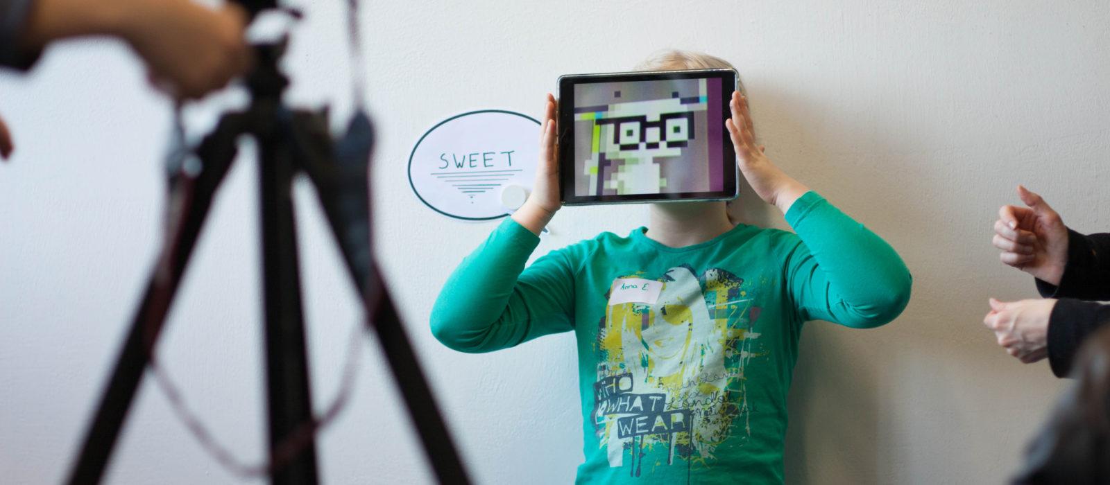 """Ein Kind hält sich bei den Aufnahmen zum Projekt """"Museum macht stark"""" ein Tablet vor das Gesicht"""