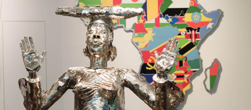 Menschenskulptur aus Metall vor Abbildung des afrikanischen Kontinents