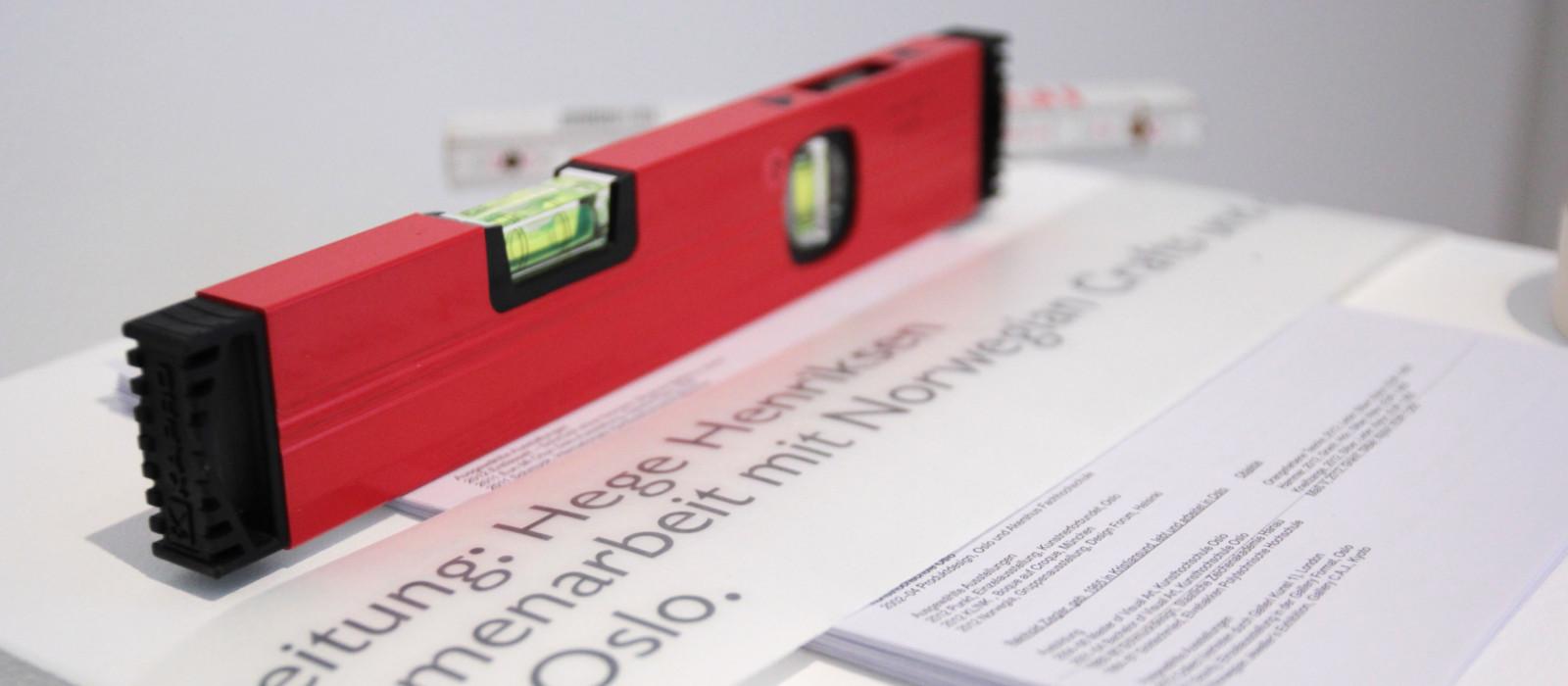 Werkzeug, das zum Ausstellungsaufbau nötig ist, liegt auf Objektlisten und Beschilderungen