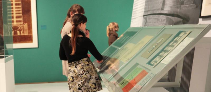 Zwei Frauen betrachten eine Vitrine mit Dokumenten und Zeichnungen