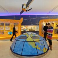 Einblick in einer Ausstellung mit Medieninstallation in Form einer Weltkugel