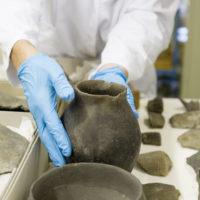 Keramik in den Händen eines Restaurators