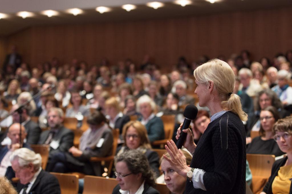 Eine Tagungsteilnehmerin beteiligt sich mit einem Wortbeitrag an der Diskussion