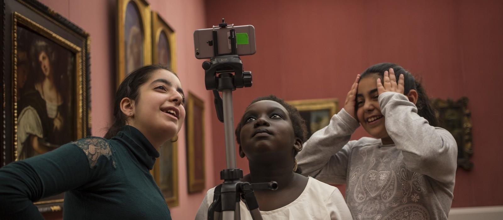 Drei Mädchen machen in einem Museum Fotos mit einem Handy