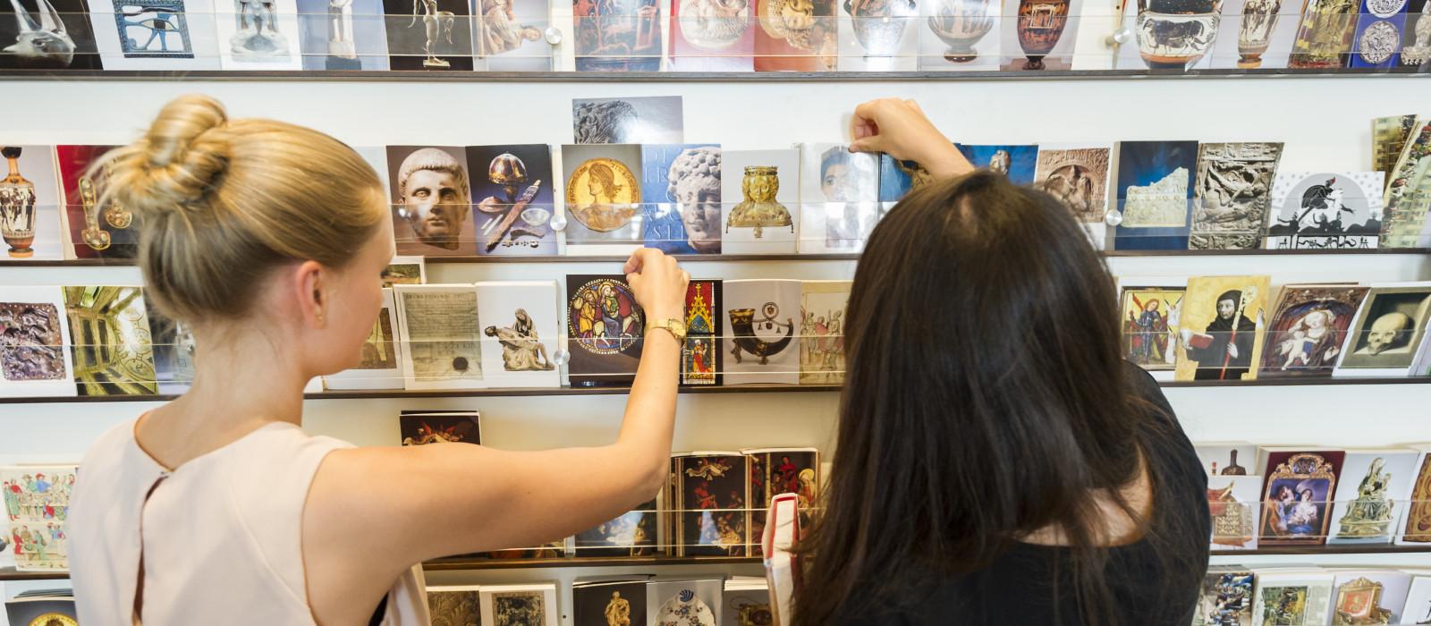 Zwei Besucherinnen schauen sich im Museumsshop die Postkartenauslage an