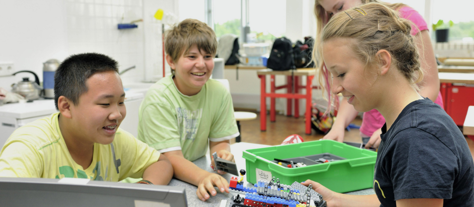 Kindergruppe beim Zusammenbauen eines technischen Gerätes mit Lego