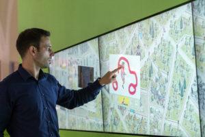 Ein Besucher vor einem interaktiven Stadtplan