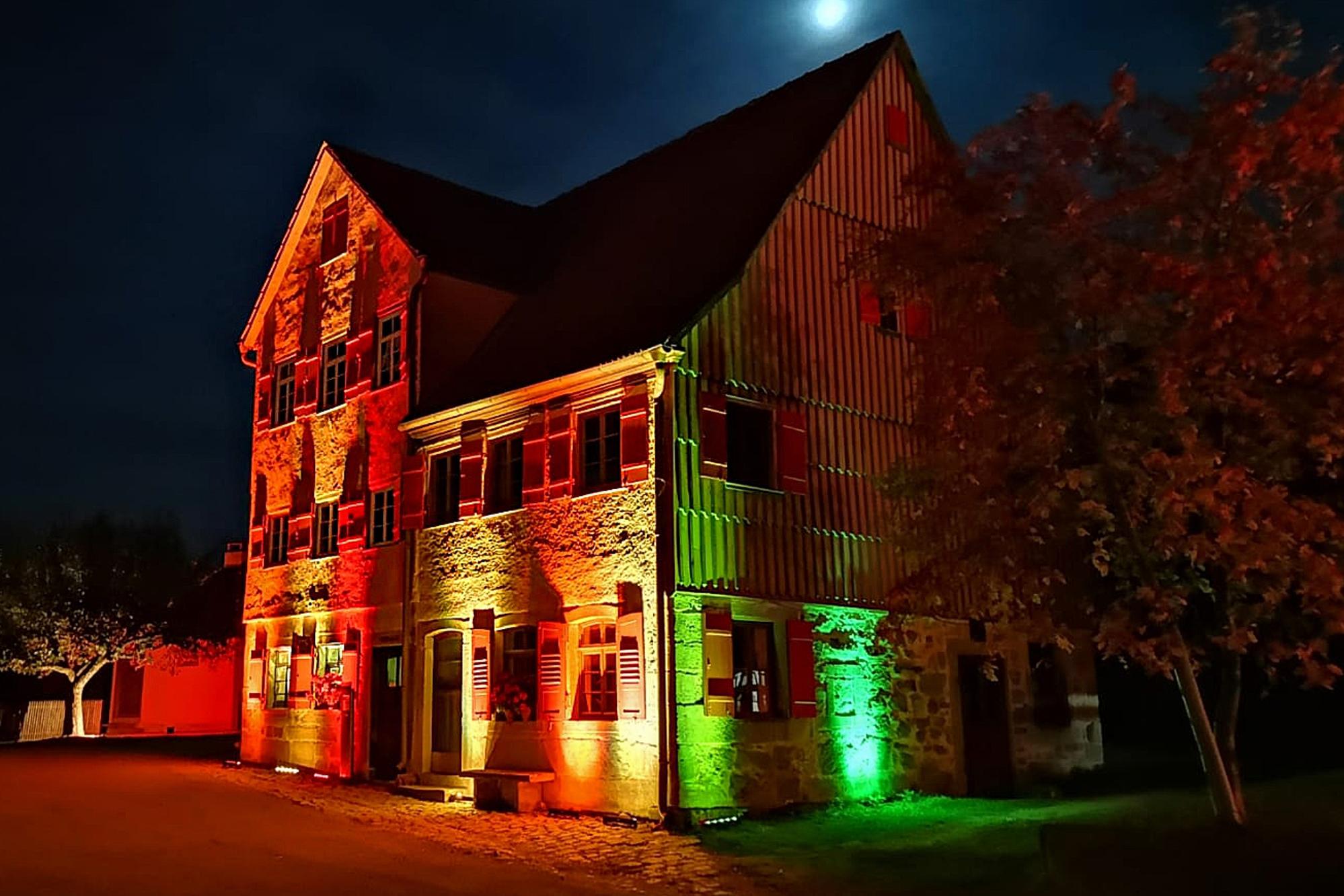Historisches Wohnhaus bei Nacht mit bunter Beleuchtung in Wackershofen